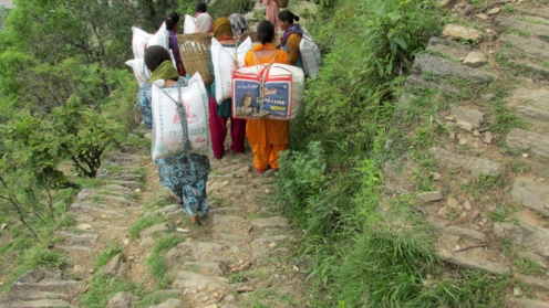 Women carrying bags of rice and flour return to their village